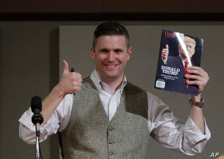 Richard Spencer, who leads a movement that mixes racism, white nationalism and populism, holds up a magazine cover showing President-elect Donald Trump before signing it for a supporter, Dec. 6, 2016, in College Station, Texas.