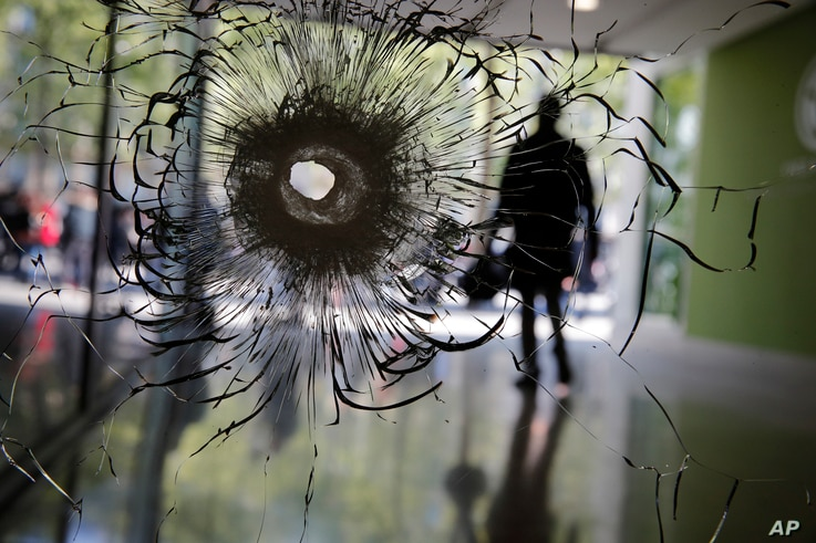 A bullet hole is pictured on a shop window on the Champs Elysees boulevard in Paris, April 21, 2017.