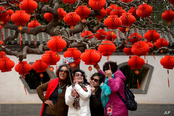 Chinese women share a light moment as they take a selfie near a tree decorated with red lanterns ahead of the Chinese Lunar New Year at Ditan Park in Beijing, Jan. 30, 2019.