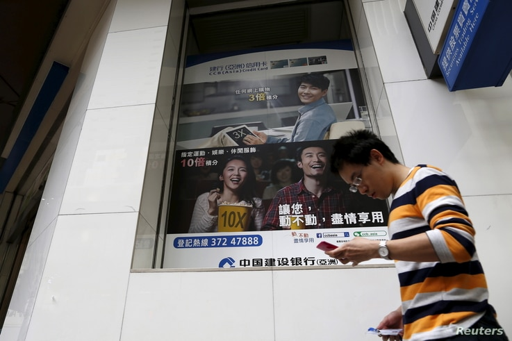 A man checking his smartphone walks past a bank advertisement in Hong Kong, China, Nov. 30, 2015. Recent research indicates that outlay on digital advertising in China has surpassed the amount spent on traditional ads.
