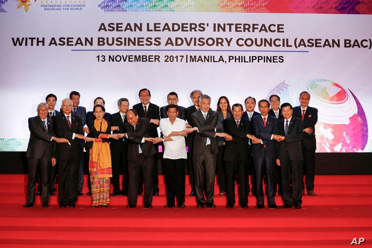 Philippine President Rodrigo Duterte, front center, links arms with heads of state and government participating in the ASEAN Summit in Manila, Philippines, Nov. 13, 2017.