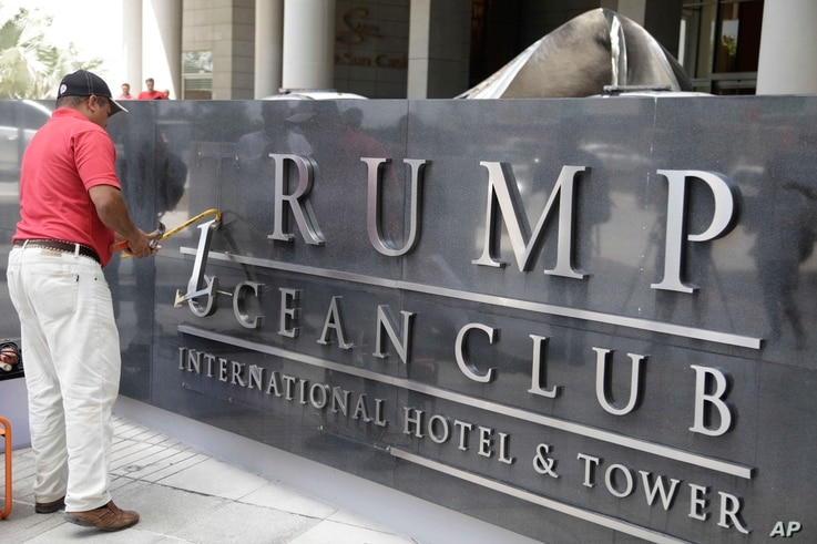 FILE - A man removes the word Trump off a marquee outside the Trump Ocean Club International Hotel and Tower in Panama City, March 5, 2018.