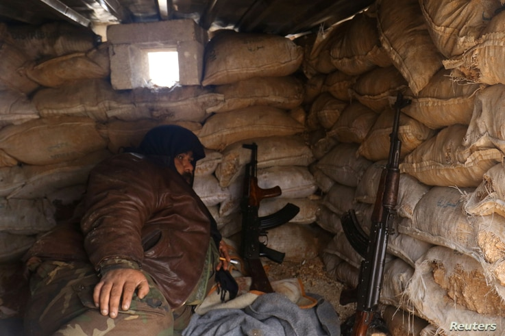 A rebel fighter rests with his weapons behind sandbags at insurgent-held al-Rashideen, Aleppo province, Syria, Dec. 30, 2016.