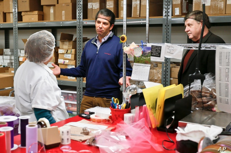 Republican Rick Saccone, right, and Donald Trump Jr., talk with chocolate workers as they take a tour of Sarris Candies during a campaign stop in Canonsburg, Pennsylvania, March 12, 2018.