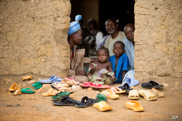FILE - Refugees sit at the door of their home at the Minawao Refugee Camp in northern Cameroon.