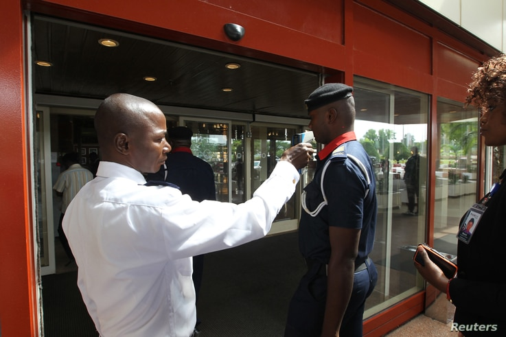 A security officer screens a man's temperature at the entrance of Transcorp Hilton hotel in Abuja, Sept. 3, 2014.