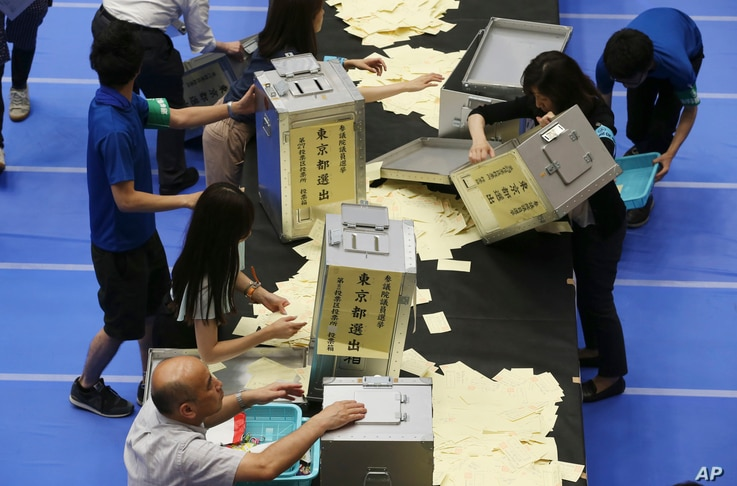 Election staff members open ballot boxes for vote counting in the upper house elections at a ballot counting center in Tokyo on July 10, 2016.