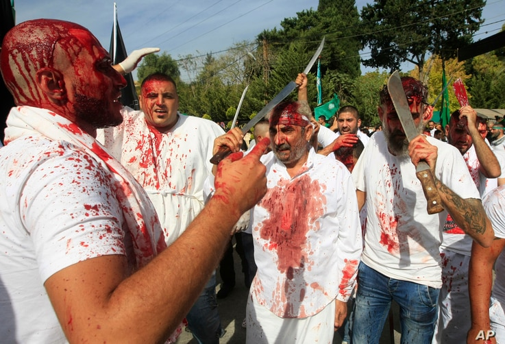 Lebanese Shi'ite men bleed from self-inflicted head wounds as they strike themselves with swords to show their grief during Ashura rituals, in the southern market town of Nabatiyeh, Oct. 12, 2016.