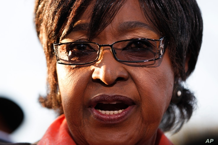 Winnie Madikizela-Mandela addresses the media in front of the house of her former husband and former South African President Nelson Mandela in Soweto, June 28, 2013.