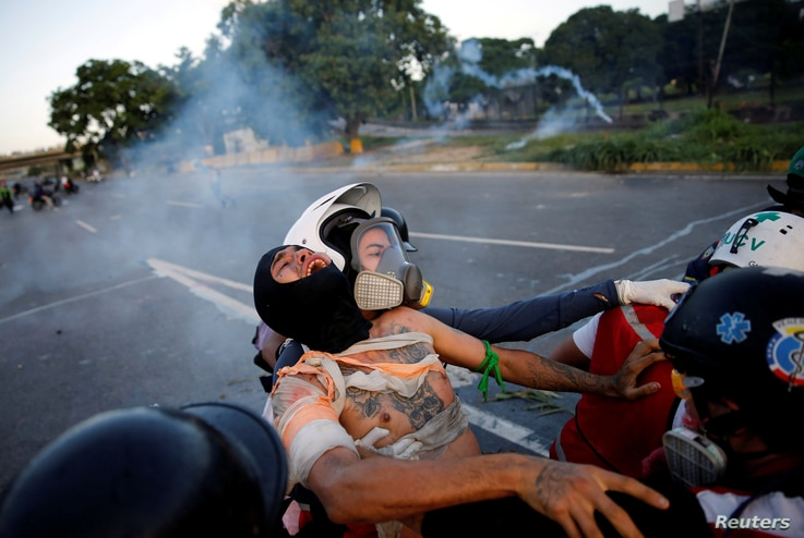 An injured opposition supporter is helped by volunteer members of a primary care response team during clashes with riot security forces at a rally against Venezuelan President Nicolas Maduro's government in Caracas, Venezuela, June 22, 2017.