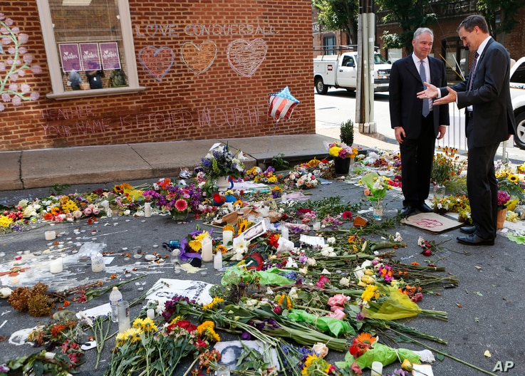 Sen. Tim Kaine, left, and Charlottesville mayor Michael Signer visit a makeshift memorial Aug. 16, 2017, where Heather Heyer was killed when a car rammed into a crowd of people protesting a white nationalist rally Charlottesville, Va.