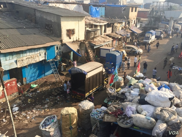 A street along Mumbai's Dharavi slum in India is littered with waste that includes plastic items and bags.