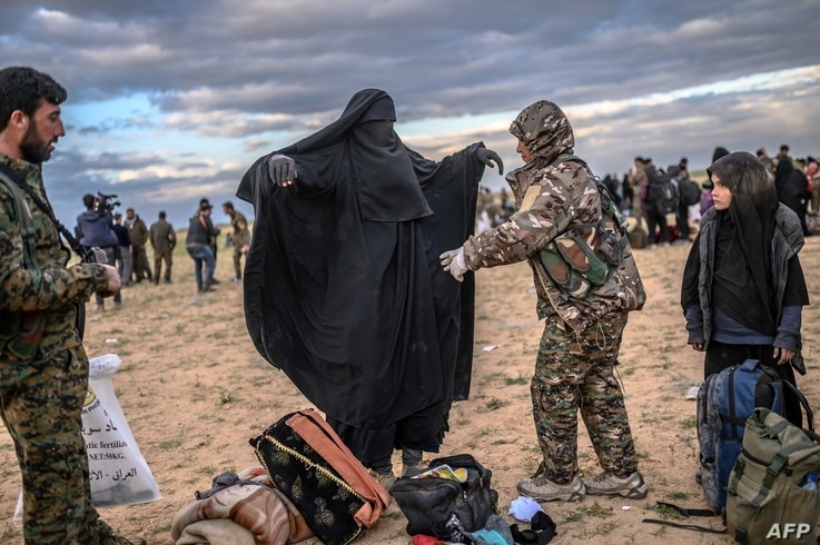 A member of the Kurdish-led Syrian Democratic Forces (SDF) searches a woman after she left the IS group's last holdout of Baghuz, in Syria's northern Deir Ezzor province, Feb. 27, 2019.