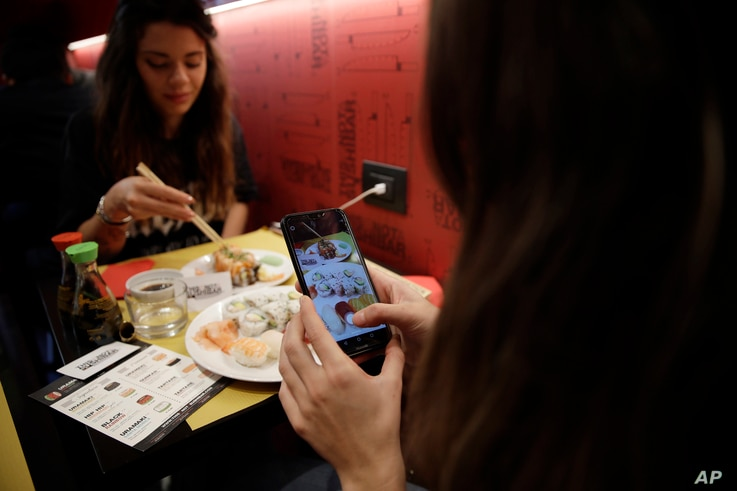 Chiara Valenzano, right, photographs her food as she has lunch with her friend Giulia Terranova at the 'This is not a Sushi bar' restaurant, in Milan, Italy, Oct. 16, 2018. At the restaurant, payment can be made according to the number of Instagram f...
