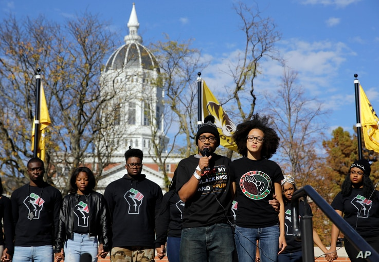 Jonathan Butler, front left, addresses a crowd following the announcement that University of Missouri System President Tim Wolfe would resign Nov. 9, 2015, at the university in Columbia, Mo.
