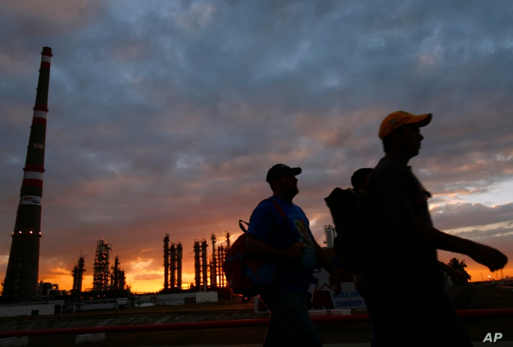 FILE - Workers leave their shift as Cubans prepare to inaugurate the Camilo Cienfuegos refinery in Cienfuegos, Cuba, Dec. 20, 2007.