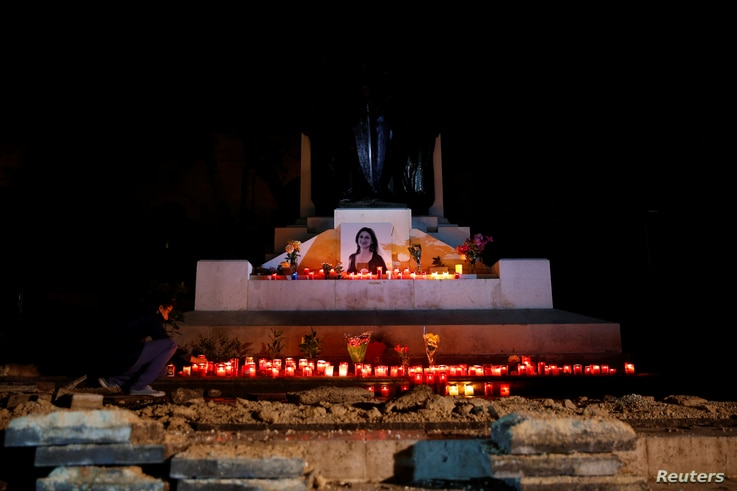 An activist places candles and flowers on the Great Siege monument, after rebuilding a makeshift memorial to assassinated anti-corruption journalist Daphne Caruana Galizia, in Valletta, Malta, Nov. 16, 2018.