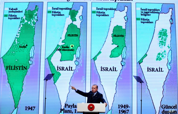Backdropped by maps of Israel and the Palestinian Territories, Turkey's President Recep Tayyip Erdogan, gestures as talks at the closing ceremony of exporters' innovation and entrepreneurship week event, in Istanbul, Saturday, Dec. 9, 2017. Erdogan h...
