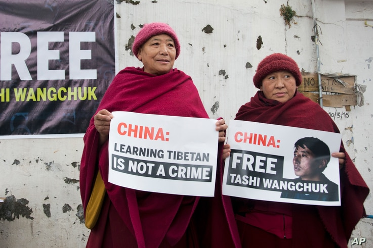 FILE - Two Tibetan nuns in Dharmsala, India, hold placards demanding that China release Tashi Wangchuk, an outspoken campaigner for the rights of Tibetans, Jan. 27, 2017.