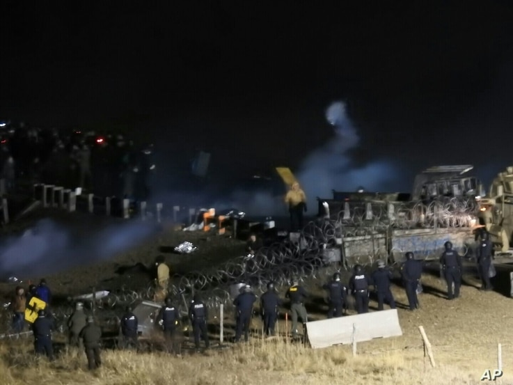 In this image provided by Morton County Sheriff's Department, law enforcement and protesters clash near the site of the Dakota Access pipeline, Nov. 20, 2016,.