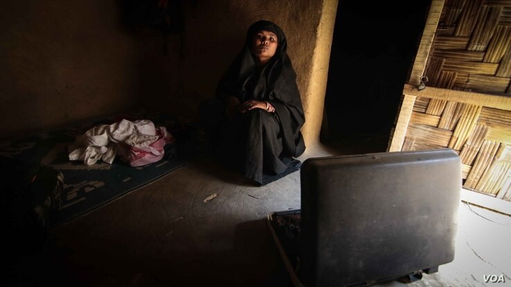 Rashida at home with a suitcase containing the clothes of her son Mohammed, 10, who vanished a month ago. (J. Owens/VOA)