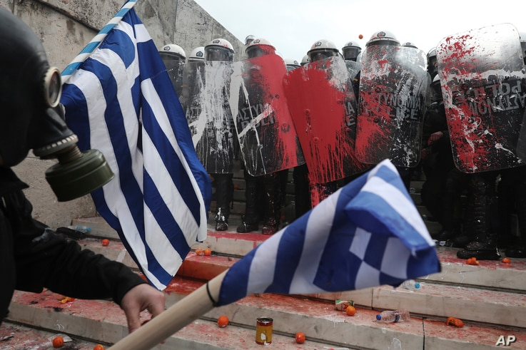 Greek riot police block the stairs leading to parliament during clashes after a rally in Athens, Jan. 20, 2019.