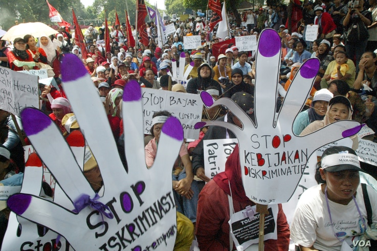 Indonesian women shout slogans while they rally outside the presidential palace in an International Women's Day rally in Jakarta March 8, 2006.   REUTERS/Dadang Tri - RTR1C7LJ