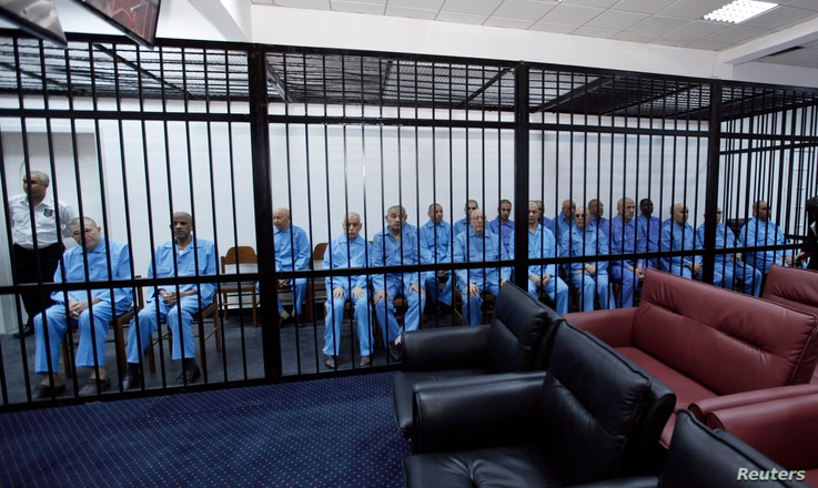 Officials of Muammar Gadhafi's government sit behind bars during a hearing at a courtroom in Tripoli, Libya, April 27, 2014.