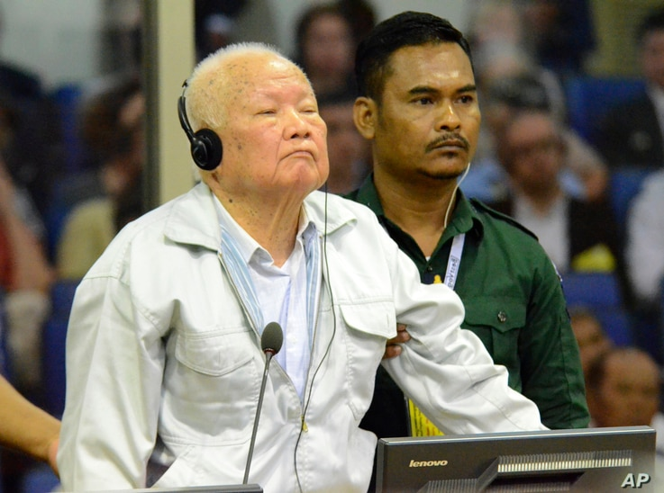 In this photo released by the Extraordinary Chambers in the Courts of Cambodia, Khieu Samphan, left, former Khmer Rouge head of state, stands at the dock in a courtroom during a hearing at the U.N.-backed war crimes tribunal in Phnom Penh, Cambodia, ...