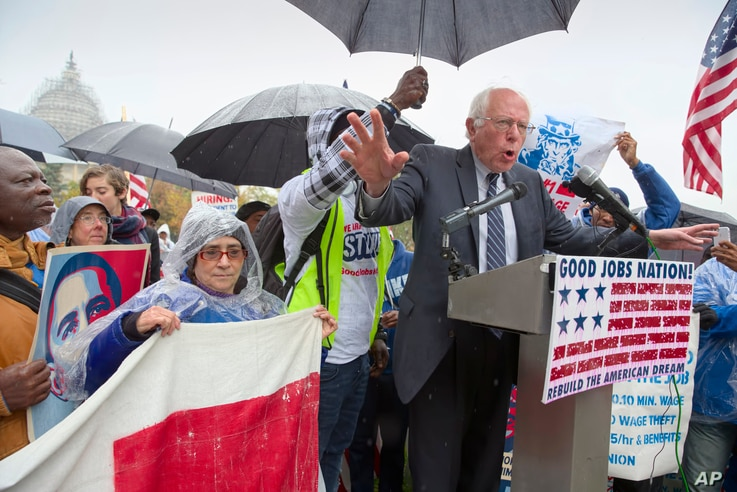 FILE - Democratic presidential candidate Sen. Bernie Sanders joins low-wage workers, some who cook and clean at the U.S. Capitol, at a rally to protest what they describe as poverty pay, Capitol Hill, Washington, Nov. 10, 2015.