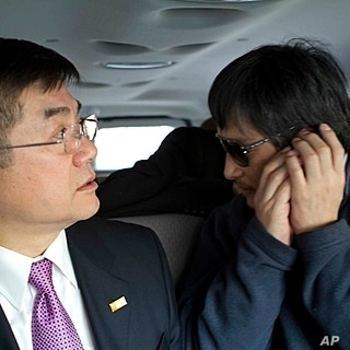 In this photo released by the US Embassy Beijing Press Office, blind lawyer Chen Guangcheng makes a phone call as he is accompanied by U.S. Ambassador Gary Locke on the way to a hospital in Beijing, May 2, 2012.