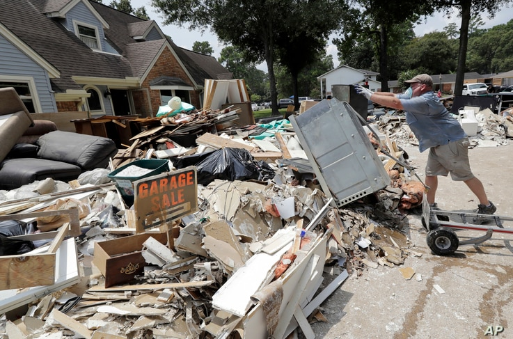 Volunteer Paul Hancock pushes an oven damaged by floodwaters onto a pile of debris in the aftermath of Hurricane Harvey on Sunday, Sept. 3, 2017, in Spring, Texas. Hancock and numerous other volunteers are helping flood victims across the Houston are