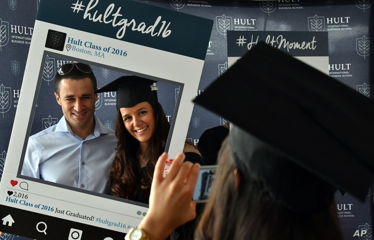 Hult International Business School graduate Victoria Stanciu and her fiance pose as her classmate takes a photo  after the graduation ceremony in Boston