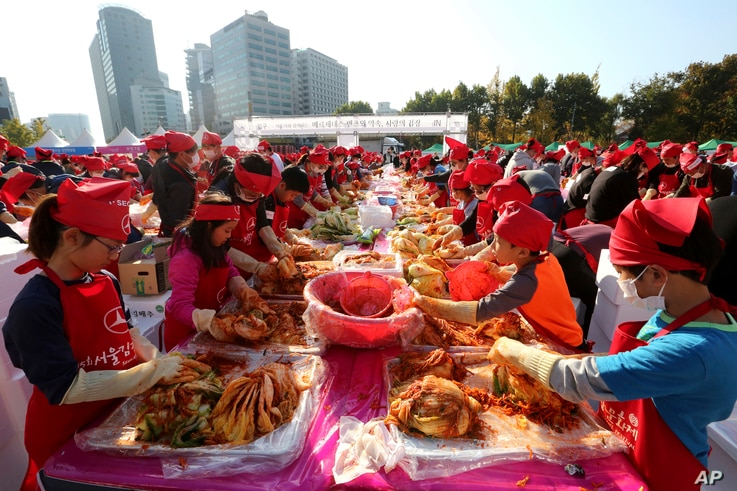 Participants make kimchi, a staple Korean side dish made of fermented vegetables, for a Guinness World Record for the largest number of people making kimchi at one place during the Seoul Kimchi Festival at Seoul Plaza in Seoul, Sunday, Nov. 4, 2018.