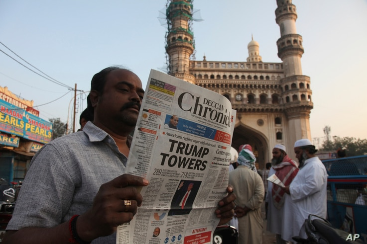 """An Indian man reads a newspaper near the Charming monument that has the headline """"Trump Towers """" to refer to U.S President-elect Donald Trump's victory in Hyderabad, India, Thursday, Nov. 10, 2016."""