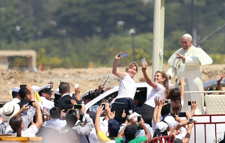 Pope Francis waves to the crowd as he rides in the popemobile through Samanes Park, where he will celebrate Mass, in Guayaquil, Ecuador, Monday, July 6, 2015. A crowd estimated at 1 million people, greeted Francis on the packed dirt of Samanes Park f...