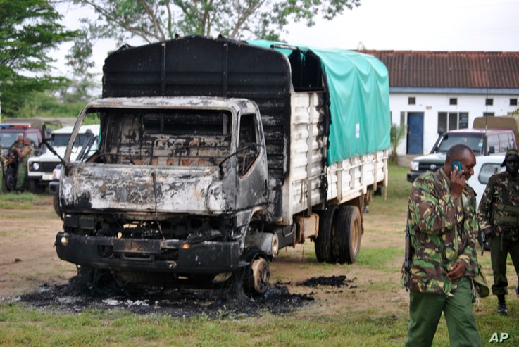 Policemen stand near the wreckage of a burnt vehicle after gunmen attacked outside Gamba police station in Gamba, Kenya, July 6, 2014.
