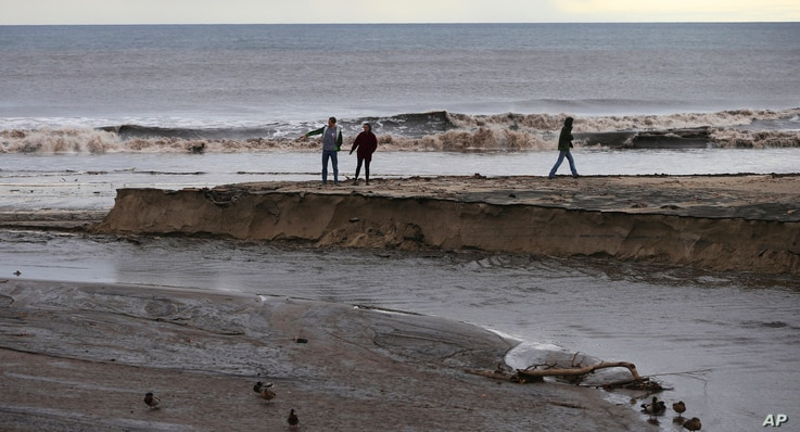 Waves loaded with mud and debris crash on the beach where Trancas Creek flows into the Pacific Ocean in an area burned by the Woolsey Fire in Malibu, Calif., Dec. 6, 2018.