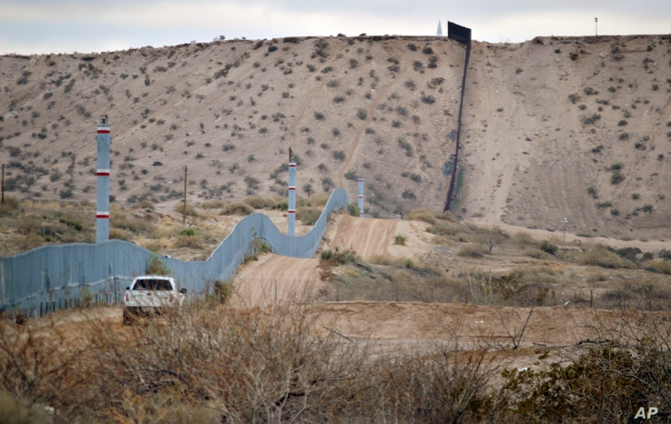 FILE - A U.S. Border Patrol agent drives near the U.S.-Mexico border fence in Sunland Park, New Mexico, Jan. 4, 2016. Trump pledges to replace the fence with a wall that Mexico will pay for.