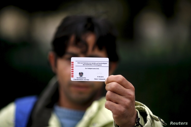 Omar shows the back of his Austrian migrant card in Traiskirchen, Oct. 13, 2015.