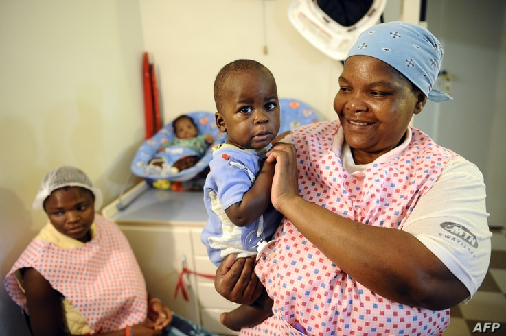 FILE - A nurse plays with an orphan in Bulembu, Swaziland, March 1, 2012.