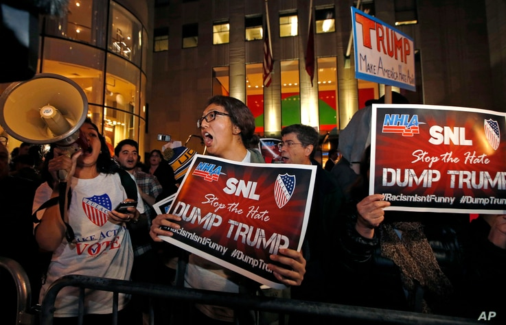 """Protesters opposed to the appearance of Republican presidential candidate Donald Trump's appearance as a guest host on this weekend's """"Saturday Night Live,"""" shout anti-Trump slogans in front of NBC Studios in New York, Nov. 4, 2015"""