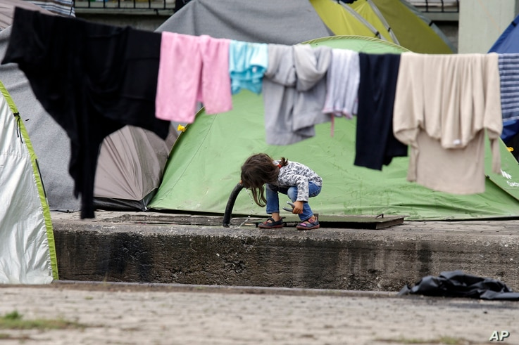 A child drinks water  from a pipe on the platform of a train station which was turned into a makeshift camp crowded by migrants and refugees at the northern Greek border point of Idomeni, Greece, May 2, 2016.