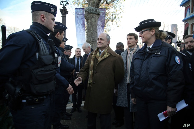 French Interior Minister Bruno Le Roux, center, shakes hand with police officers during a visit to see the police presence securing the Champs Elysees, in Paris, Sunday, Dec. 11, 2016.