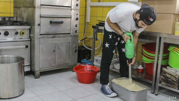 Hassan Mansour from Aleppo, Syria, prepares a daily meal at the Khora center, in the Exarchia district in Athens, Greece, Oct. 24, 2016.