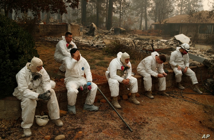 Members of the California Army National Guard take a break at they search burned homes for human remains at the Camp Fire, Nov. 15, 2018, in Paradise, Calif.