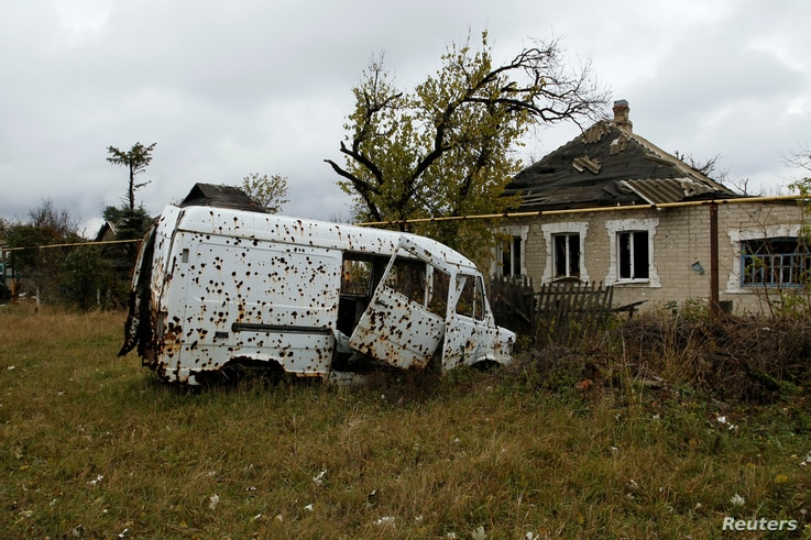 A vehicle damaged by shrapnel and explosions sits abandoned in the Oktyabrsky district in Donetsk, Ukraine, Nov. 1, 2017.