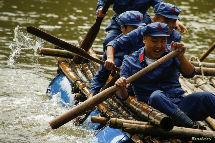 Participants race on a raft across a lake during a Communist team-building course extolling the spirit of the Long March, organized by the Revolutionary Tradition College, outside Jinggangshan, Jiangxi province, China, Sept. 14, 2017.