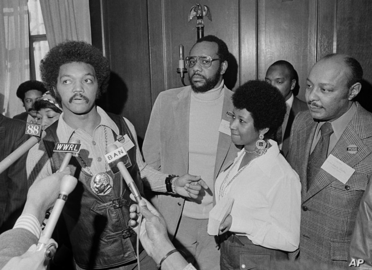 FILE - The Rev. Jesse Jackson speaks to reporters at the Operation PUSH Soul Picnic in New York, March 26, 1972, as Tom Todd, vice president of PUSH, from second left, Aretha Franklin and Louis Stokes look on.