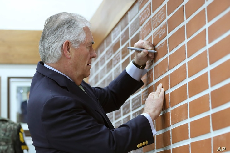 U.S. Secretary of State Rex Tillerson writes a message for soldiers on a brick wall before the lunch meeting at the Camp Bonifas near the border village of Panmunjom, which has separated the two Koreas since the Korean War, in Paju, South Korea, Marc...